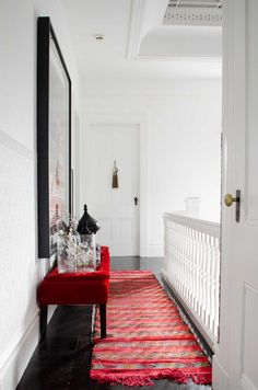 White hallway with red runner on @thouswellblog