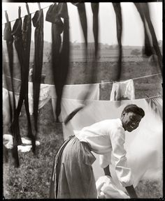 UNITED STATES - CIRCA 1902: A young African American woman working in the midst of clotheslines heavy with sheets and stockings.