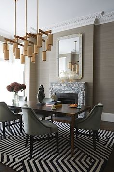 Dramatic dining room with striped area carpet and modern chandelier