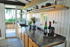 """Køkkenet fra Uno Form i egetræ er helt klassisk med en række underskabe og åbne væghylder. Blandingsbatteri i rustfrit stål fra Vola. Bordpladen i granit """"fortsætter"""" ud til udekøkkenet, man går ud til via stalddøren og gentager Kjærholm-mantraet: Inde integreret med ude."""