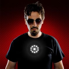 """""""Tony Stark Light up LED Iron Man Shirt Well, if you want to be light Tony Stark you have to have an arc reactor in your chest. This Tony Stark Light up LED Iron Man Shirt will put one on your chest. While it may not save your life and p. Iron Man Halloween Costume, Stark Industries, Tony Stark, Mens Tees, Man Shirt, Cool Shirts, Light Up, Look, Cool Stuff"""