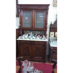 """Ένα μοναδικό έπιπλο, που αναδεικνύει τους Έλληνες τεχνίτες της εποχής του 1900 μέχρι 1930. Το πάνω μέρος διαθέτει δίφυλλο ντουλάπι με υπέροχο κρύσταλλο εποχής και δύο ράφια εσωτερικά. Το κάτω μέρος έχει δύο συρτάρια και ένα δίφυλλο ντουλάπι με ένα ράφι εσωτερικά. Τα σκαλίσματα εξωτερικά με τους περίτεχνους κρίνους, που δένουν αρμονικά με τις κολώνες, που μιμούνται τα φύλλα του λουλουδιού, δίνουν σε αυτό το κομμάτι """"άρωμα"""" Ελλάδας. 'Ενα συγκλονιστικό κομμάτι σε τιμή πρόκληση!"""