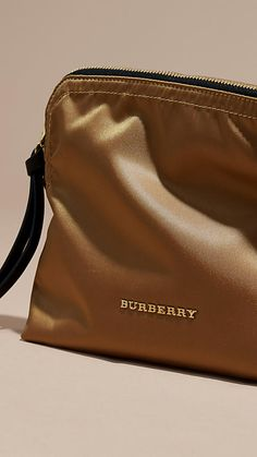 A durable Burberry pouch with a zip-top closure and leather zip pull. This versatile piece works as a beauty bag or clutch, with protective lining lending a functional edge.