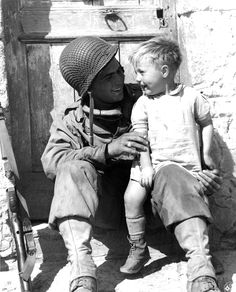 U.S. Army Pfc. Fred Linden of Detroit, Michigan, 38th Infantry Regiment, 2nd Infantry Division, holds a young French boy following the liberation of the village of Trévières during the Battle of Normandy. Trévières, Calvados, Lower Normandy, France....