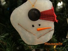Melted Snowman Ornament -   You will need:  wax paper  hot glue  two black seed beads (for eyes)  scrap of fabric (for scarf)  the bottom part of a leaf (small enough to be arms)  top hat and carrot miniatures  cord