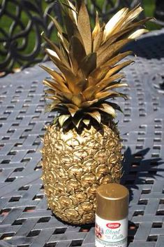 Pineapples float! Spray painted gold pineapple for centerpiece...may be a simple idea??? brown coconuts and gold pineapple...