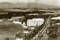 The Moana Surfrider as it appeared in 1926, with the construction of the Royal Hawaiian Hotel in the background.