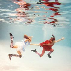 """Elena Kalis, a Russia-born artist resides in Bahamas. She re-interpreted one of the best known tales in history – """"Alice in Wondland """". She made her daughter, Sascha, to play as Alice in her remarkable """"Alice in Waterland"""" underwater photo shoot. Her photographs are amazingly colourful, surrealist, dreamy with lots of fantasy."""