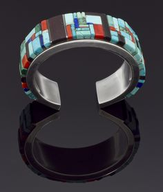 1970′s Charles Loloma bracelet inlayed with turquoise, ironwood, Mediterranean coral, and lapis.  Measures 5 1/4″ with a 1″ opening.  1 1/8″ width.