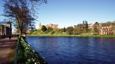 A view across blue water of the River Ness on a clear, sunny day along the Ness Islands Walk.