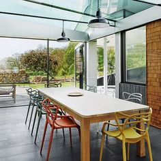Modern glass dining area with colourful chairs. Dining room design ideas – furniture, lighting, wallpaper, dresser – by House & Garden. Conservatory Dining Room, Dining Room Chairs, Dining Room Furniture, Dining Area, Furniture Design, Modern Conservatory Furniture, Pool Chairs, Modern Chairs, Outdoor Wicker Chairs