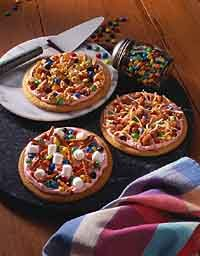 "Mini Pizza Cookies: 1 tube (20 ounces) refrigerated sugar cookie dough; 2 cups (16 ounces) prepared pink frosting; ""M's""® Chocolate Mini Baking Bits; Variety of additional toppings such as shredded coconut, granola, raisins, nuts, small pretzels, snack mixes, sunflower seeds, popped corn and mini marshmallows"