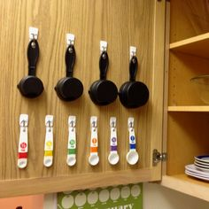 "Never lose a measuring cup or spoon to the ""utensil junk door"" again! Hang measuring spoons and cups on the inside of the cabinet using Command™ Brand Hooks."