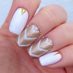 Simple yet beautiful looking white and gold nail art design. The base color is white while the patterned design on top is painted with gold glitter.