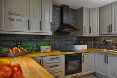 Kitchen, butcher block countertop, stone backsplash, black range, grey cabinets