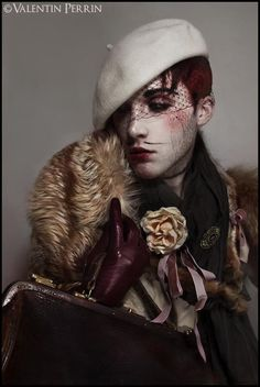 Found : Valentin Perrin official site. Time period: Circa 2005  This is a good representation of a dandy. This explains dandyism through the use of blush and the hat with the netting. The fur coat, red gloves, and flower also stylize the outfit to stand out. This also seems to be a reference back to an older period, with the muted colors and pose of the model.