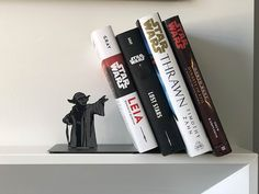 A Metal Jedi Master Yoda Bookend That Appears to Use the Force to Hold Up Books