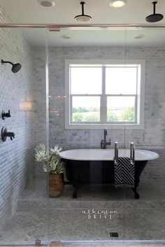 This master bathroom has a giant wet area covered in marble tiles  with four shower heads and a vintage-inspired clawfoot tub!