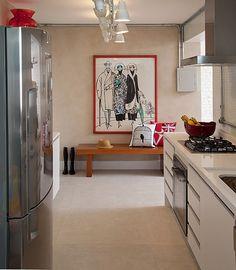 O quadro grande, com moldura colorida, anima a cozinha em tons neutros da arquiteta Valeria Bartholi