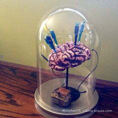 Mad scientist brain Halloween deco. Brain in a jar, or under glass dome, glass cloche. Vials with blue liquid pushed into brain which is held up by a candle holder. Old motor component is wired to brain. - Halloween prop, decoration