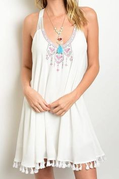 This sleeveless flowy dress features a multicolored embroidered neckline, a…