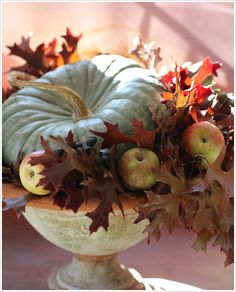 Pretty Fall arrangement using a blue pumpkin, apples and leaves in an urn.  from florali