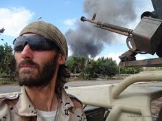 Matthew VanDyke next to the KADBB Desert Iris jeep and DShK machine gun during the Battle of Sirte, Libya War