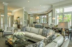 Another view of the open floor plan in this new Hilton Head Island home. We see the family room space with the dining area behind and the open kitchen beyond...all tied together with beautiful wood look porcelain tile flooring. What a great overall look - serene,