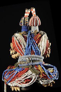 Poupée traditionnelle liée aux culte de fertilité. Au Cameroun, quand un jeune homme Fali se fiance, il fabrique une poupée en bois (ham pilu) et la décore de cheveux, de perles et de petits objets qu'il offre ensuite à sa fiancée. Elle la portera ensuite, gage d'une promesse de famille nombreuse et de beaux enfants.