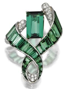 GREEN TOURMALINE AND DIAMOND BROOCH, VERDURA, 1948.  The brooch designed as a curling ribbon tendril framing an emerald-cut tourmaline weighing approximately 7.50 carats, completed by  baguette and calibré-cut tourmalines, the inside fold of the ribbon and the baton terminals pavé set with small round diamonds, signed Verdura.