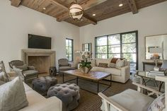 Transitional living room features a wood plank ceiling accented with Zodiac Pendant with White Glass illuminating matching face to face sofas in natural linen slipcovers along with a wood herringbone top coffee table and a pair of round gray velvet tufted ottomans. Living room boasts a pair of gray French cane chairs flanking a gray rope stool placed in front of a composite fireplace accented with a herringbone firebox under a flatscreen TV