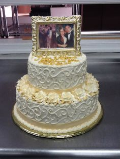 Ivory and gold 50th Wedding Anniversary Cake. Topper is a white chocolate picture frame painted with edible gold dust framing edible picture images of the anniversary couple.