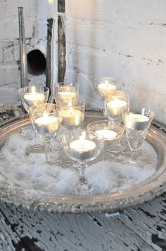 Votives in vintage stemware. I want to do this with little red hot candies in the bottom of the glasses!