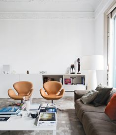 the Barcelona apartment designer Elina Vila D'Acosta-Calheiros shares with her husband, Ginés Gorriz, Arne Jacobsen Swan chairs join a sofa by Piero Lissoni for Living Divani. The cabinet is from Cappellini, as is the Marcel Wanders Big Shadow lamp.