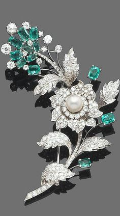 An emerald, cultured pearl and diamond spray brooch The floral spray composed of single-cut diamond leaves, the flowerhead set with similarly cut diamonds and an 8.9mm. cultured pearl centre, with oval mixed-cut emerald highlights, the flowerhead mounted en tremblant, diamonds approx. 5.15ct. total, length 8.7cm.