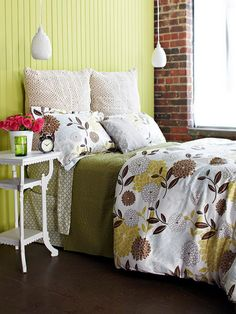 Trade a traditional headboard for a fun paneled wall to add color and interest. The fresh green wall and beautiful exposed brick anchor this youthful room. Choose a white nightstand and light fixtures for contrast. A bedspread containing browns and greens brings the earthy look full circle.