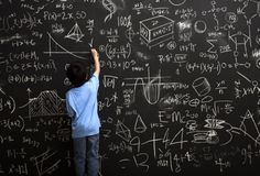 A young boy stands drawing on a huge chalkboard filled with mathematical equations (Quelle: Justin Lewis)