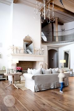 Love the simple furnishings, chandelier, ceiling, railing....and the fast-moving kiddo to remind us real people live there!