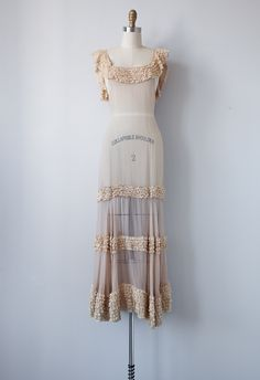 1930s full length gown in pale cafe au lait color. The softly sweeping neckline features rows upon rows of layered lace. Back has romantic draping bedecked with tiny ruffles. The long floor length skirt features tiers of ruffles. Dress is completely sheer.