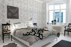 swedish bedroom - chairs for sidetables + great wallpaper all in shades of grey with high contrast black and white accents