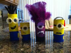 Despicable Me family movie night. DIY minions made out of toilet paper rolls, paint, water bottle caps for eyes and purple feathers for the purple minions hair.