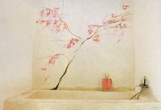 in the bathroom a wallpainting of a branche with blossoms