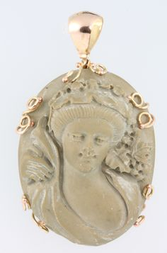 Lot 564, A yellow gold lava cameo pendant in the form of a semi-clad lady, est £170-200