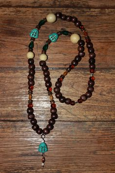 Necklace with brown & beige wood beads, brown glass beads, coconut shell rondelles, green crystal faceted teardrops & Turquoise Buddha Heads. 25 €