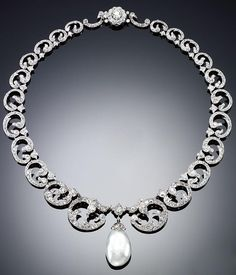 DIAMOND AND PEARL NECKLACE, LATE 19TH CENTURY. Designed as a series of graduated scrolls set with circular-, rose-cut and cushion-shaped diamonds, suspending a natural pearl drop, length approximately 400mm