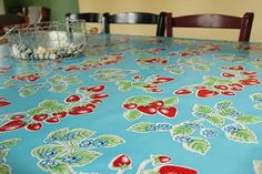 Oilcloth table cover- cut oil cloth to size, and staple to the underside of the table.  Easy to clean, and bright!