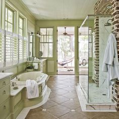 Cool Master Bathroom, love the rustic look of the green cabinetry and exposed brick wall.