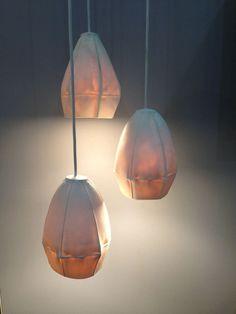 The Kawa Pendants from Souda are made of porcelain using a slip-casting technique. Light shines through highlighting the surface textures and details of each piece.