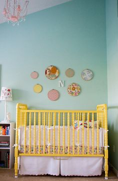 love the yellow crib! ...especially with this wall color and the pink chandelier.