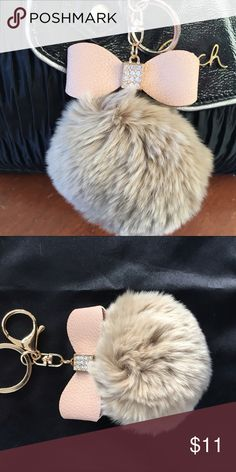 New Rabbit Fur Pom Pom Keychain Handbag Decor New never used. Real Rabbit fur. Color is like a beige/tan.Has a bow with rhinestones on it. Can use as a keychain or hang it on your handbag. I have a few of these in different colors. Handbag not for sale. Used only to show how this looks on a handbag only. Accessories Key & Card Holders